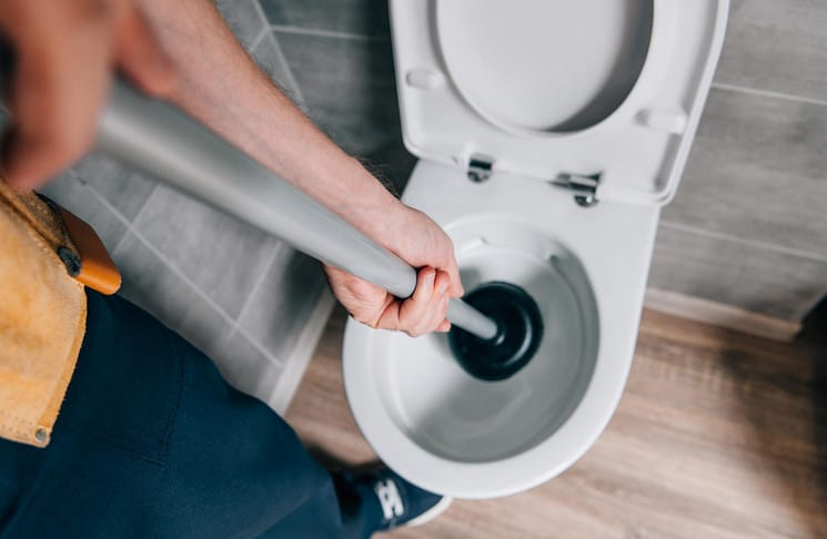 plumber unblocking a clogged toilet with a plunger
